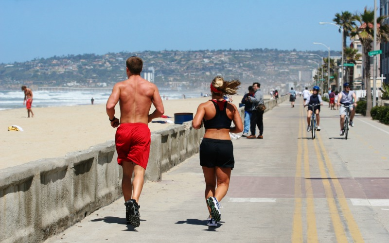 Couple Running on Mission Beach Boardwalk, San Diego Rental Income Property